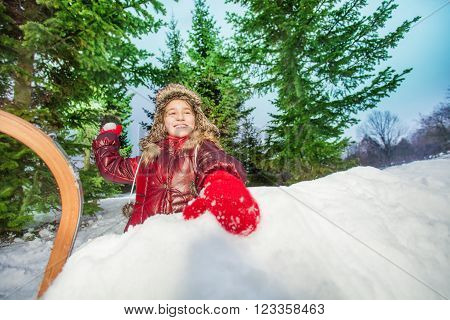 Cute girl holding up a snowball with a cheeky smile outdoors on a winter's day