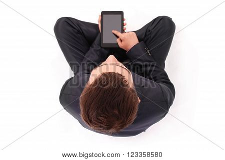 Boy in black suit sit and hold tablet PC isolated on white. Shallow depth