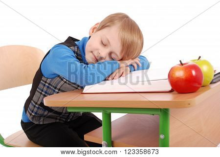 Boy fell asleep at a school desk isolated on white