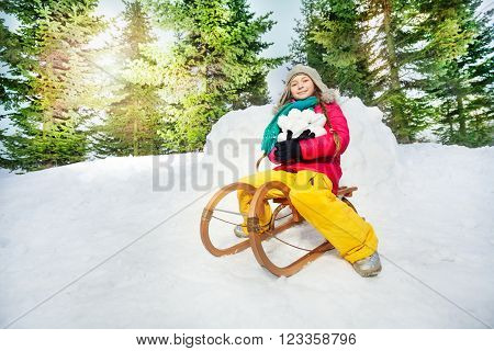 Girl sitting on the wooden sledge and holding snowballs at the sunny winter day