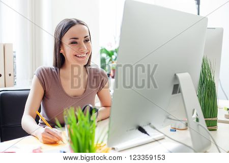Attractive woman is using a computer for work. She is sitting at the desk and writing. The lady is smiling happily