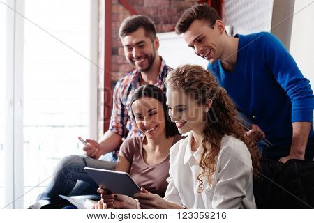 Cheerful young creative team is watching a tablet together. The women are sitting with joy. The men are standing and smiling
