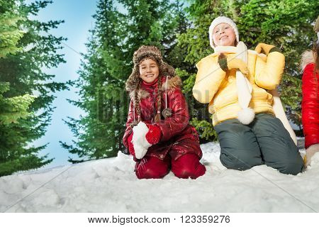 Two happy girls playing the snowball in the winter forest