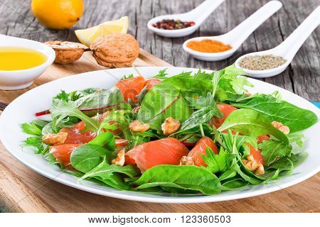 Red fish salad with mixed lettuce leaves on a white dish on a cutting board with olive oil and spice close-up top view