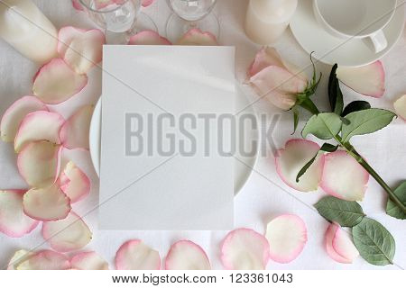 Wedding table menu mockup with Rose and petals. Mockup with a vertical card on a plate