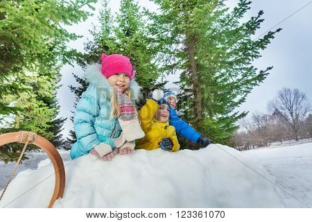 Kids boys and girls behind snow fortress wall throw snowballs