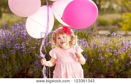 Baby girl 3-4 year old holding balloons outdoors. Birthday party. Childhood. Happiness.