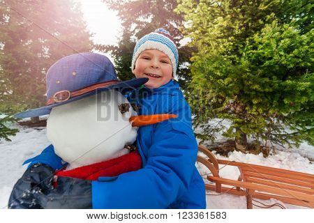 Happy little boy hug snowman outside in the park