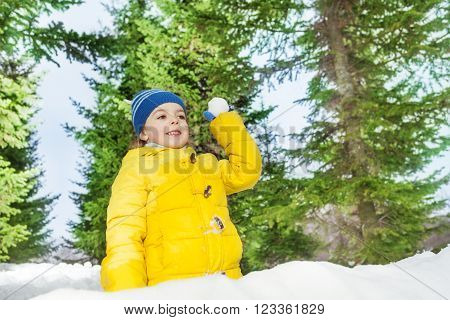 Little boy with snowball play outside on winter day among trees in yellow coat