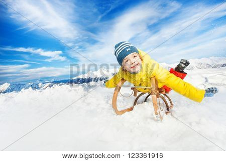 Little boy in yellow coat on sledge and stretched hands in the mountain