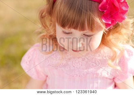 Cute baby girl 3-4 year old with pink flower in blonde hair outdoors. Looking down. Top view. Childhood.