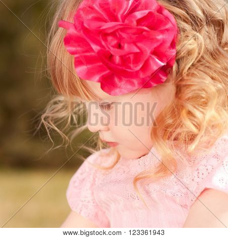 Cute baby girl 3-4 year old wearing flower hairband outdoors. Childhood.