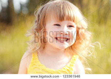 Smiling baby girl 3-4 year old walking in park outdoors. Looking down. Childhood. Playful.