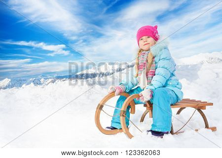 Little girl in blue on sledge in the mountains sit and look at the camera