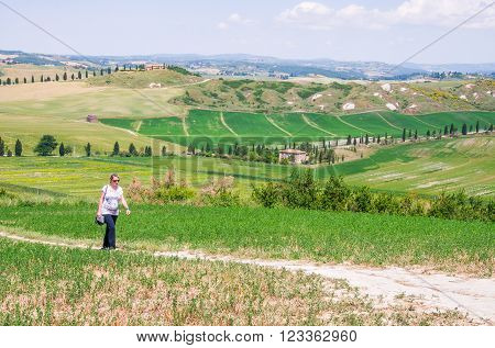 Pregnant tourist strolling through Crete Senesi during summer holidays in Italy