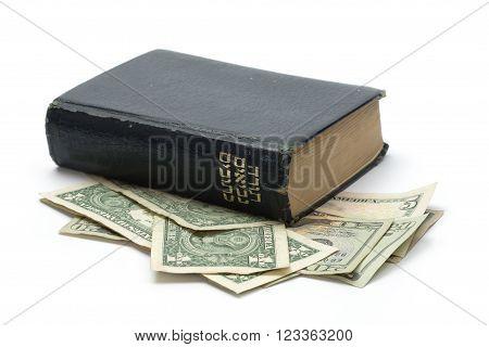 Bible book in Hebrew on top of dollar bills