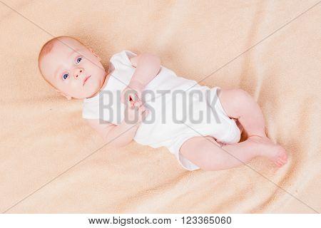 Babe boy lies in white clothes in studio