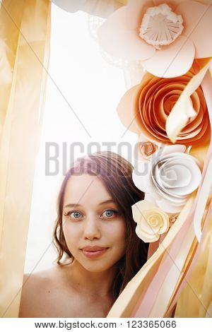 Beautiful Gentle Female among Paper Flowers Decoration and Ribbons. Headshot Woman Looking to Camera. Romantic Wedding Ceremony. Space for Your Text.
