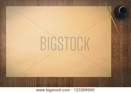 Topview of blank aged paper sheet and ink-pot on wooden table. Mock up 3D Render