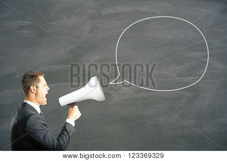 Speech bubble and caucasian businessman shouting into megaphone. Mock up