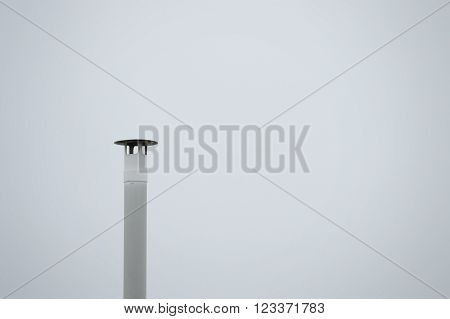 A smokestack against a grey sky. Empty copy space for editor's text.