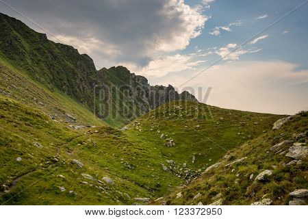 Romanian mountains, Carpathians, with green mountainsides and blue sky with clouds
