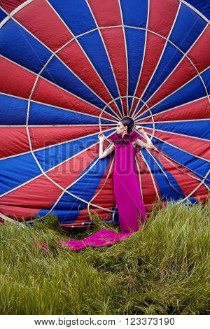 portrait of a young girl in a crimson dress with a aerostat
