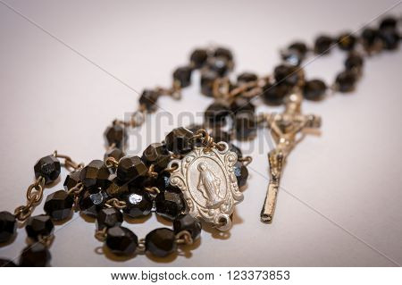 Black rosary with cross on the white background