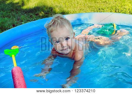 White Baby European appearance emotionally bathed in a blue pool. Toddler with toys lying in the children's pool.