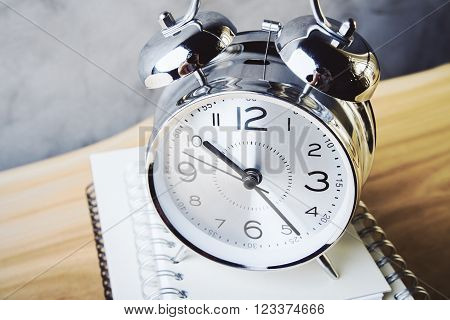 Topview of alarm clock and copybooks on wooden table