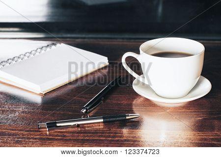 Closeup of desktop with coffee cup, two pens and notepad