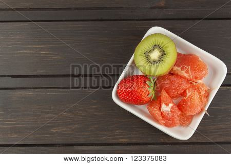 Diet program, raw food. Kiwi, strawberry and red grapefruit in a porcelain dish. Food full of vitamins.