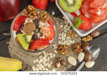 Preparing healthy breakfast for kids. Yogurt with oatmeal, fruit, nuts and chocolate. Oatmeal for breakfast. Preparing diet meals. A healthy diet for athletes.