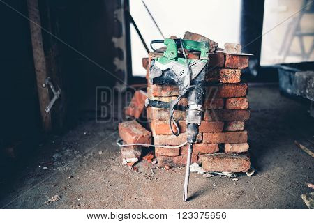 Construction tool, industrial jackhammer with demolition debris and bricks