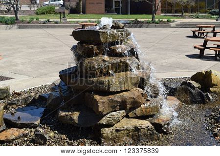 a mismatched stone water fountain surrounded by gravel.