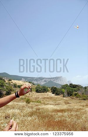 Hands Man Flying A Kite On A Background Of Mountains