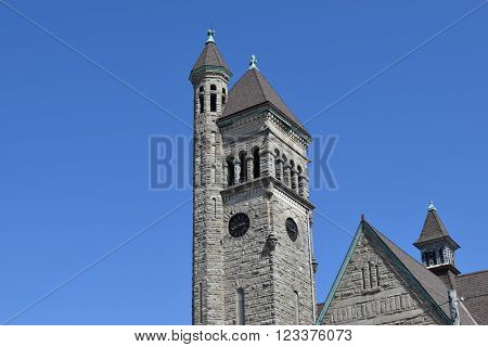 a stone church steeple with a clock in it.