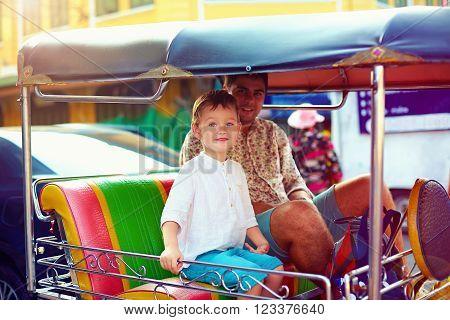 Happy Tourist Family Travel Through The Asian City On Tuk-tuk Taxi