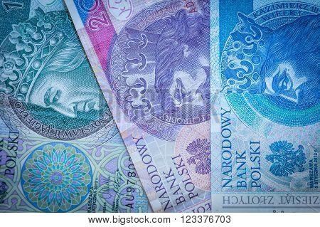 Three Polish zloty banknotes: green, pink and blue