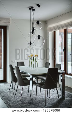Room with light walls. On the floor there are gray tiles and a gray carpet. On the carpet stands table with frosted glass tabletop and chromed legs. On the table stand 5 glass vases with yellow tulips.