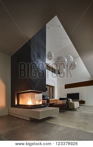 Hall in a cottage with light walls and big round decorative lamps at the top. In the front there is a glass fireplace with burning fire and a black chimney. Behind the fireplace there are two black armchairs with gray pillows, beige sofa.