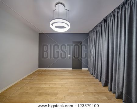 Empty room in a modern style with light parquet on the floor. Ceiling and a left wall are light gray, back wall is dark gray with dark door. There are switches with power socket close to door. On the right there are curtains. At the top there is a lamp.