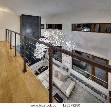 View from the 2nd floor on 1st floor hall. Hall is with light walls and big round ornamental lamps at the top. On the 2nd floor there is a parquet on the floor and a railing. On the 1st floor there is a beige sofa with pillows and plaid, dark table, two b
