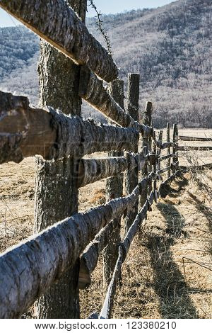 part of the wooden fence with barbed wire around the ranch