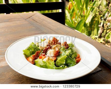 cesar salad on wooden table in restaurant