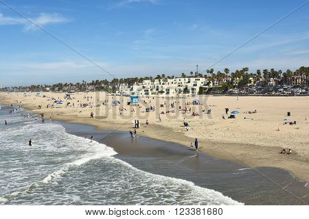 HUNTINGTON BEACH, CA - MARCH 25, 2015: Huntington Beach Shoreline with lifeguard stations and beach goers on a sunny day.