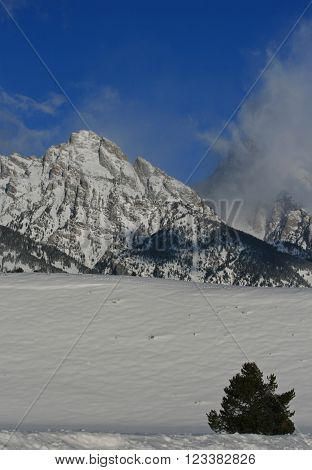 Snow clouds blowing off Grand Tetons in Grand Tetons National Park in Wyoming USA