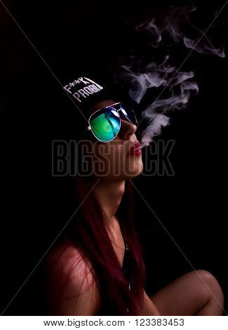 Attractive young woman in cap and sunglasses, smokes on a dark background. Be trendy, be rapper.