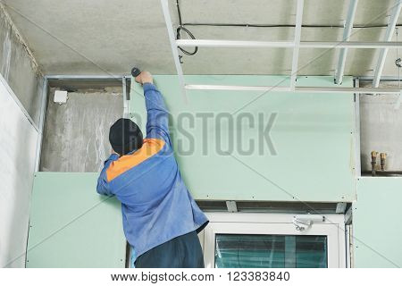 carpenter with gypsum plasterboard and screwdriver
