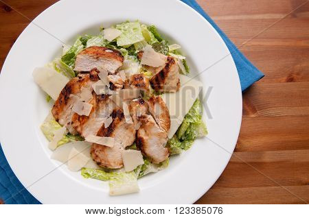 caesar salad topped with grilled chicken and shaved parmesan cheese